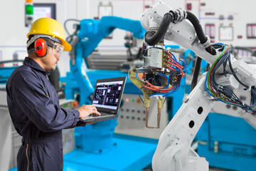Engineer using laptop computer maintenance automatic robotic hand machine tool in automotive industry, Industry 4.0 concept