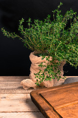 Fresh thyme in the vase on the wooden background