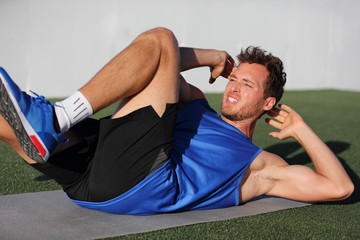 Sit ups - fitness man exercising oblique abs workout with bicycle situps outside in grass in summer. Fit male athlete working out cross training in summer. Caucasian muscular sports model in his 20s.