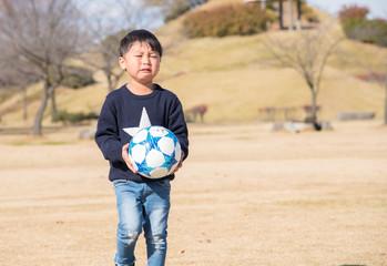 サッカーボールを持つ泣いている男の子