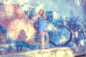 young girl posing against a wall with graffiti, the Sun, jeans stands at the painted walls.