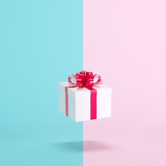 White gift box floating on blue and pink background. minimal christmas concept idea.