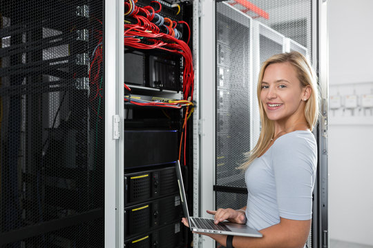 woman with laptop programing in server room