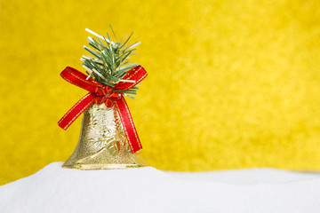 Christmas decoration, golden bell design on white snow over blurred gold background