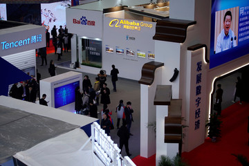 China's President Xi Jinping shown on a screen in front of logos of China's leading Internet companies Tencent, Baidu, Alibaba Group during the fourth World Internet Conference in Wuzhen