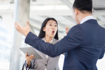 Young businesswoman holding papers talking with a businessman with anger, Boss found a mistake in documentation. Work failure concept.