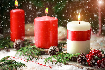 Christmas card with burning candles and decorations.