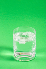 Glass with Water on Green Background