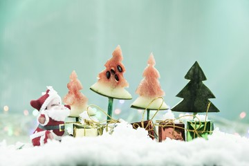 Santa is cold, children rush to pick up gifts./Christmas concept Use watermelon to make Christmas tree. Cool tone background