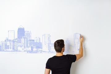 architekt zeichnet einen stadtentwurf an eine wand