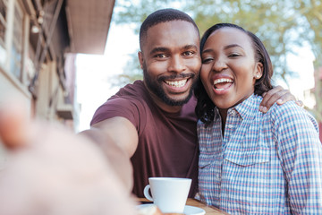 Smiling African couple taking selfies together at a sidewalk cafe