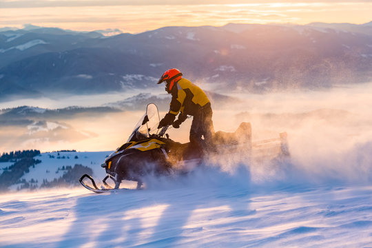 A man is ridind snowmobile in mountains.
