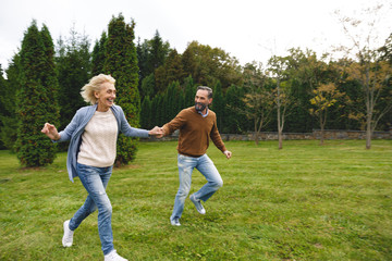 Cheerful mature couple holding hands