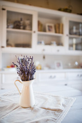 Dried lavender bunch in a white vase in vintage kitchen.