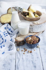 Milk in a glass and in a bottle, muesli in a blue cup. on a white wooden background and pineapple and tablecloth with blue flowers