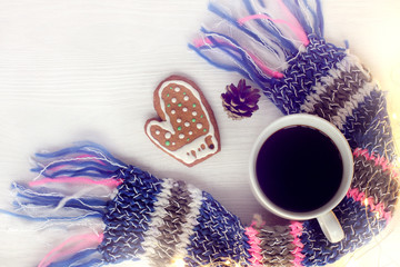 warm moments of winter holidays/ Black coffee in white mug and ginger mitten on table with festive scarf and of garland top view