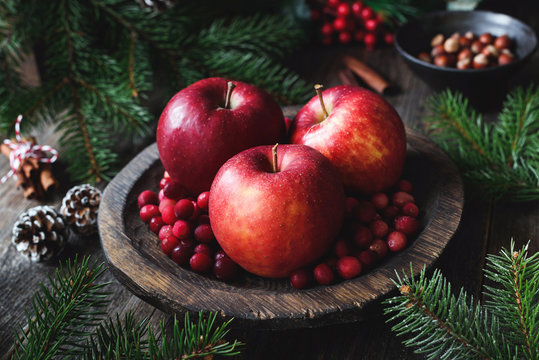 Red apples, cranberries and fir tree branches. Christmas still life. Winter wallpaper. Horizontal view