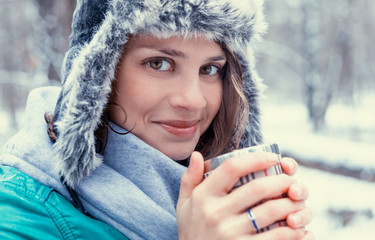 Portrait of a beautiful happy smiling young woman in a funny hat with a hat with a mug in the winter forest. Walks in winter