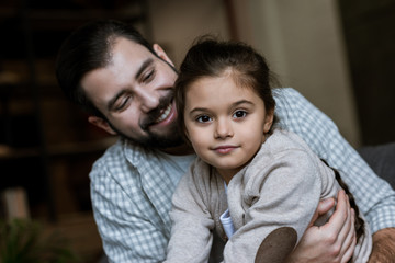 happy father and daughter hugging and looking at camera at home