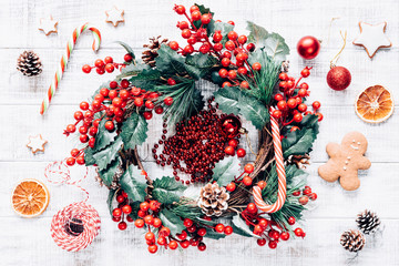 Christmas winter wreath, candy canes, Christmas tree decorations and gingerbread cookies on old white wooden background. Wallpaper, background or holiday art. Top view, high exposure