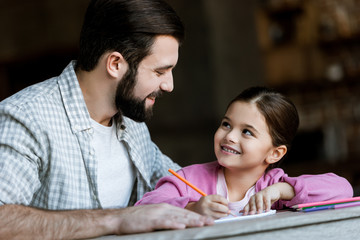 happy father with little daughter sitting at table and drawing in scrapbook at home