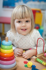 Portrait of little girl having fun at kindergarten, looking at camera