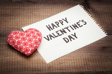 Happy Valentines card. Textile heart and sheet with text on wooden background.