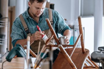 Carpenter painting wooden chair