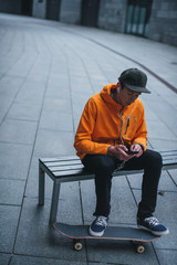 skateboarder sitting on bench and listening music with smartphone