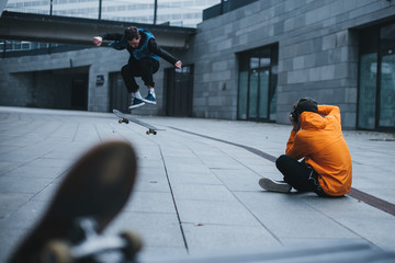 man sitting on floor and taking photo of skateboarder doing trick