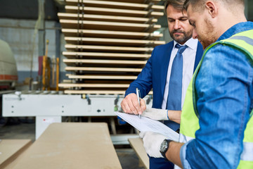 Side view portrait of handsome mature businessman signing investment paper in factory workshop standing with young workman wearing reflective jacket, copy space