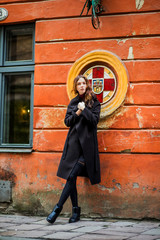 The girl in a black coat poses on the street