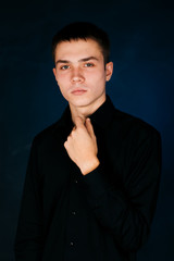 young guy on a dark studio background