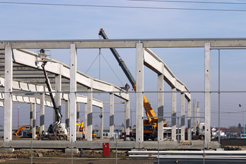 new factory construction site with trucks cranes and workers