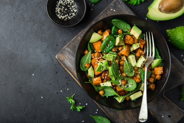 Avocado, quinoa, roasted sweet potato, spinach and chickpeas salad in black bowl.
