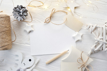 Mockup Christmas greeting card top view, flatlay on a white wooden background with a garland