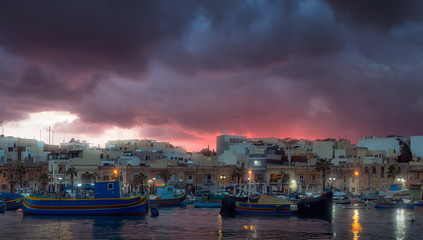 Gloomy sunset at fishing village Marsaxlokk, Malta