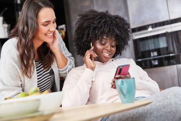Zwei junge Frauen hören Musik mit Smartphone