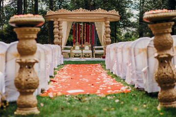 Path to the Hindu wedding altar covered with orange cloth and flower petals