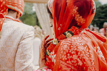 Look from behind at stunning Indian bride dressed in red lehenga and veil
