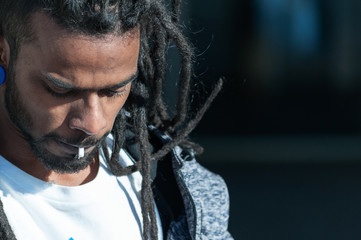 black man with dreadlocks with rolling tobacco nozzle in his mouth