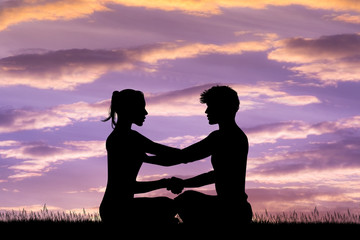 man and woman doing yoga at sunset