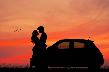 couple in the car at sunset kisses