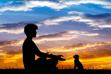 man doing yoga with dog at sunset
