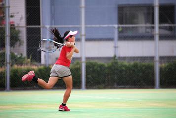 テニスでバックハンドを打つ女の子