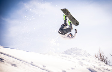 Snoboarder performing tricks on the snow