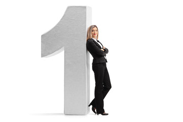 Formally dressed woman leaning against a cardboard number one