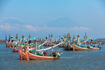 Traditional wooden fishing boats in Bugis style mooring in old fishers port on Bali island near Perancak village. Popular place to visit in Jembrana regency. Indonesia travel and culture background.