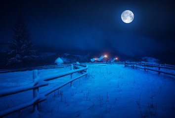 Full moon over the village covered with fresh snow