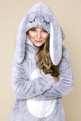 Cute, beautiful blonde young girl dressed in pajamas kigurumi with rabbit ears.